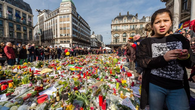 People stop and look at floral tributes at a memorial site at the Place de la Bourse in Brussels, Saturday. Brussels airport officials say flights won't resume before Tuesday as they assess the damage caused by twin explosions in the terminal earlier this week.