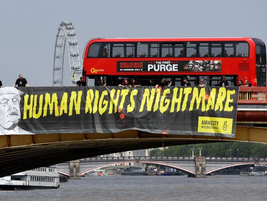 "A giant ""Human Rights Nightmare"" banner is unfurled"