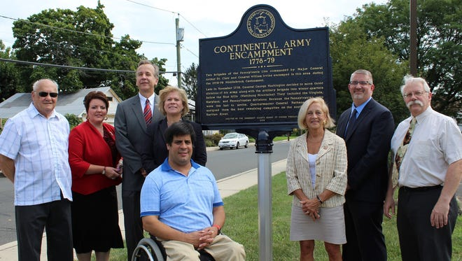 Admiring the new historical marker near the Manville Public Library are (from left) Councilman Michael Kassick, Councilwoman Michele Magnini, Mayor Richard Onderko, Borough Administrator Andrea Bierwirth, Freeholder Patrick Scaglione, Freeholder Director Patricia Walsh, county Planning Director Walter Lane and county Planner & Historic Sites Coordinator Thomas D'Amico.