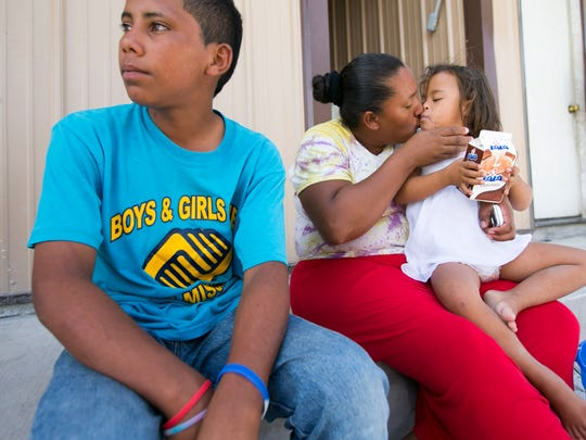 Brayan Duban Soler Redondo, 14, (left) of Quebrada Maria San Luis Conayagua, Honduras, looks on as Alba Duarte, 33, holds Anni Martinez, 5, also of Honduras. All three were at the Senda de Vida, a shelter for migrants in Reynosa, Mexico. Brayan left Honduras in mid-April to reach the United States. He and others at the shelter didn't  have the money to pay the smugglers to cross into the United States.