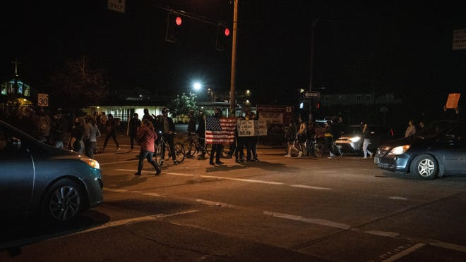 Demonstrators cross a street in a peaceful march in Eugene on Monday night. They were accompanied by a few vehicles throughout the march as well. The group dispersed around midnight. [Dana Sparks/The Register-Guard] - registerguard.com