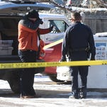 Fort Collins Police investigators photograph a possible piece of evidence on Orchard Place in west Fort Collins on Monday after a woman was assaulted and robbed.