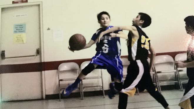 Marco Tejada, 12, saves the ball from going out of bounds during a recent parochial league basketball game between his team, the St. Raphael Stallions, and the St. Pius X Rams. Marco is the point guard for St. Raphael, where he is in the sixth grade. St. Raphael won the game.