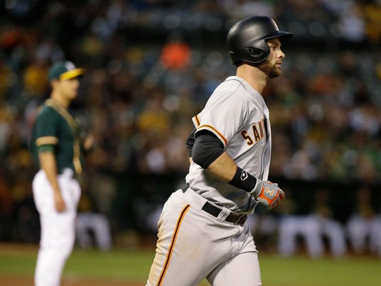 San Francisco Giants' Brandon Belt, right, circles the bases after hitting a home run off Oakland Athletics relief pitcher Michael Brady, left, in the fourth inning of a baseball game Tuesday, Aug. 1, 2017, in Oakland, Calif. (AP Photo/Eric Risberg)