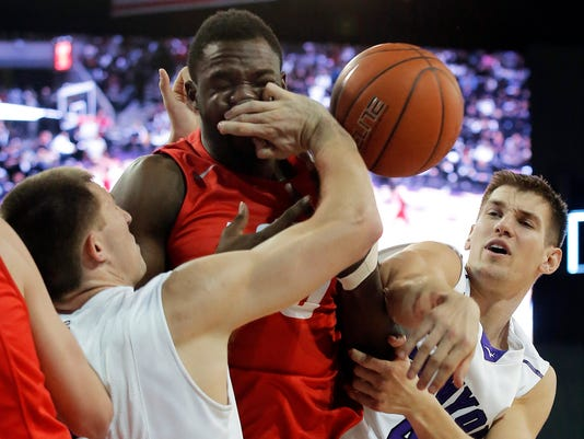 Grand Canyon's DeWayne Russell, left, and Ryan Majerle vie for the ball with New Mexico center J.J. N'Ganga during the first half of an NCAA college basketball game, Tuesday, Dec. 23, 2014, in Phoenix. (AP Photo/Rick Scuteri)