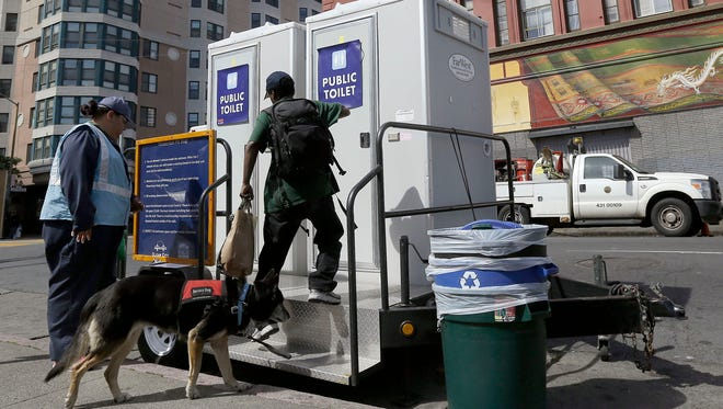 In this March 19, 2015 photo, Clean City attendant Erica Corona, left, watches as Sabrina Hollier walks up a step to use a public toilet at the Tenderloin Pit Stop in San Francisco. Not far from the fancy stores of San Francisco's Union Square, solar-powered flushing toilets on wheels roll in four afternoons per week in the dense Tenderloin neighborhood. (AP Photo/Jeff Chiu)
