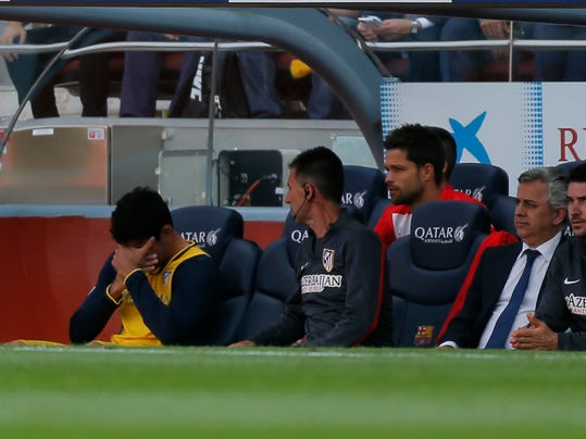 Atletico's Diego Costa, left covers his face after leaving the field injured during a Spanish La Liga soccer match between FC Barcelona and Atletico Madrid at the Camp Nou stadium in Barcelona, Spain, Saturday, May 17, 2014. (AP Photo/Andres Kudacki)
