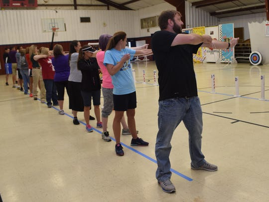 Andrew Strong (front, right), physical education teacher at Jena Junior High School, was one of about 20 P.E. coaches learning the fundamentals of archery Thursday at St. Frances Cabrini Elementary School. Training was provided through Archery in Louisiana Schools with the Louisiana Department of Wildlife and Fisheries. The coaches can then teach the sport to their students.