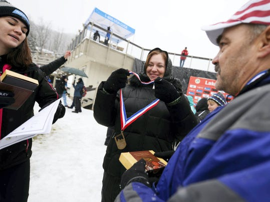 Summer Britcher offloads her medals to her mom, Carrie Britcher, and dad, Bill Britcher, after the luge World Cup at the Olympic Sports Complex in Lake Placid, N.Y., earlier this month. Summer Britcher lives at the complex almost year-round.