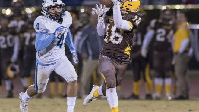 Golden West's Ian Kelly takes a pass in stride ahead of Central Valley Christian's Jaalen Rening in a Central Section Division IV quarterfinal Friday, November 18, 2016. Kelly scored on the play.