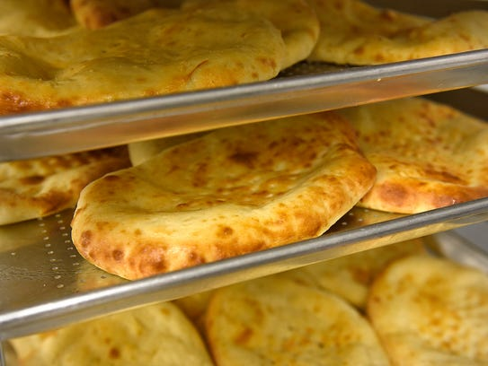 Trays of freshly-baked naan rest before being packaged