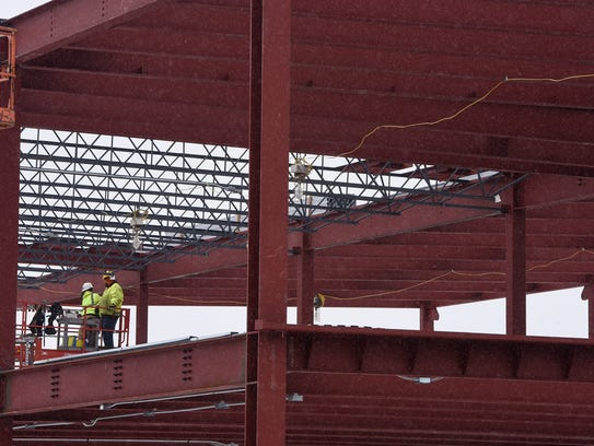 Workers are dwarfed by steel framework at the construction
