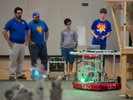 SPAM mentors George Fountoulakis, left, and George Wallace, second from left, watch as SPAM members Lucas DeBonet, 15, part of the programming team, and Tyler Woods, 18, driver and SPAM team captain, test their robot, 'Buzz Lightgear.'