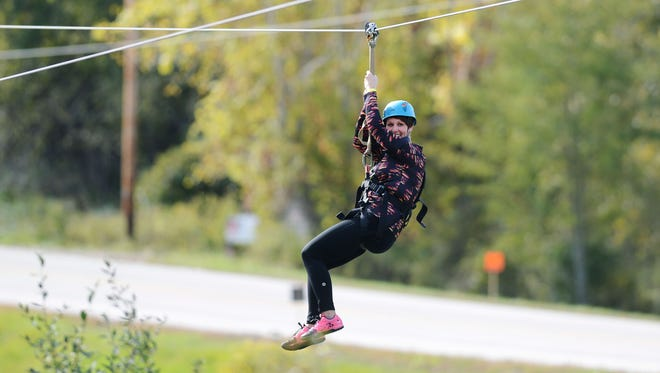 Brittany Hegner of Kaukauna travels down the zip line Oct. 10 at the NEW Zoo Adventure Park in Suamico.
