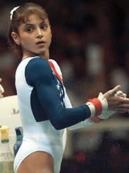 Dominique Moceanu chalks her hands before practicing