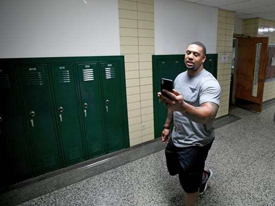 LaMarr Woodley records a video on his phone while walking the halls at The Woodley Leadership Academy in Saginaw.