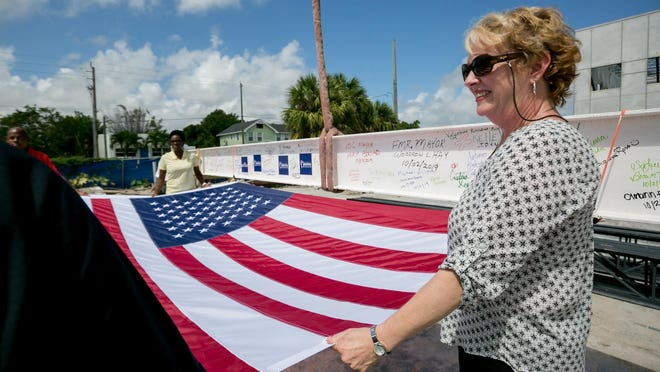 City manager Lori LaVerriere holds a flag during a topping out ceremony with a 1,400 pound, 40 foot long steel beam that will be housed in the City Commission Chambers' ceiling of the new City Hall & Library in Boynton Beach on October 2, 2019.