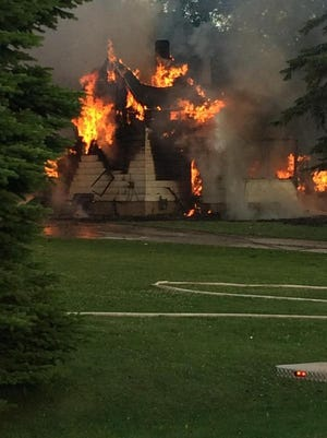 Flames shoot through the roof and windows of a house at 2368 S. Overland Road in Hobart last week. The cause remains under investigation.