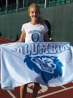 Natalie Tanner stands with Columbia Lions flag after gaining second-team All-American status in the women's 5,000 at the NCAA Championships.