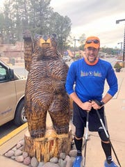 Bucklew stopped to pose with one of Ruidoso's treademark bear carvings.