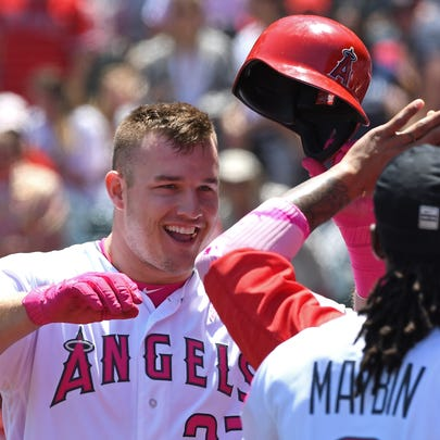 Mike Trout of the Angels is greeted in the dugout after