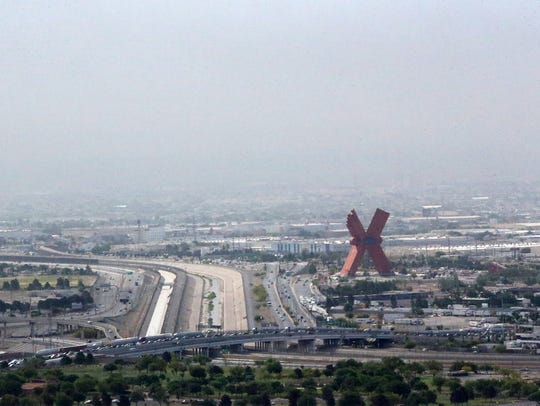 "Heavy smoke is visible over the giant red ""X"" sculpture"