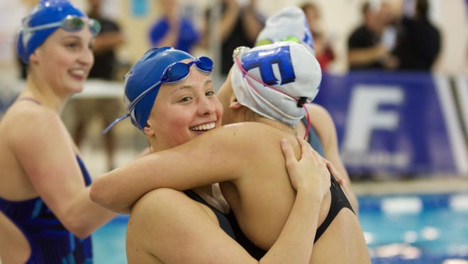 Ali Terrell (left) hugs Jessie Fraley (right), after the 100 backstroke final.