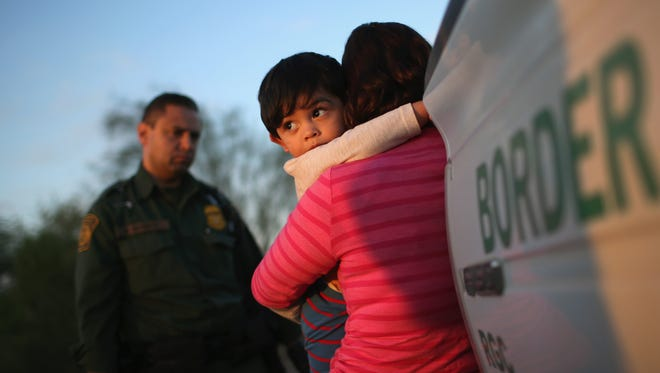 A 1-year-old from El Salvador clings to his mother after she turned themselves in to U.S. Border Patrol agents. They are part of a growing group of migrants to the U.S. who are fleeing gang violence in Central America.