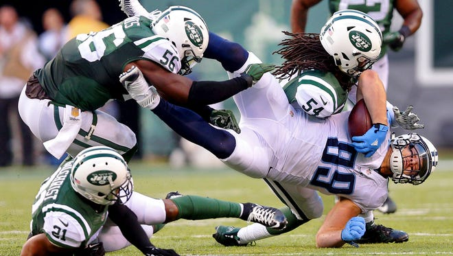 Titans tight end Phillip Supernaw (89) is tackled by New York Jets linebacker Jamari Lattimore (54) and linebacker Demario Davis (56) and safety Marcus Gilchrist (21) during the fourth quarter.