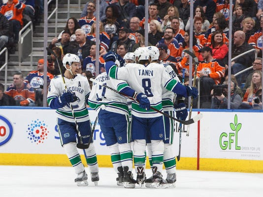 Vancouver Canucks celebrate a goal by Brandon Sutter, obscured at back right, against the Edmonton Oilers during the second period of an NHL hockey game Saturday, Jan. 20, 2018, in Edmonton, Alberta. (Jason Franson/The Canadian Press via AP)