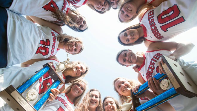 The Worcester Prep girls lacrosse team members huddle with their trophies after a perfect season.