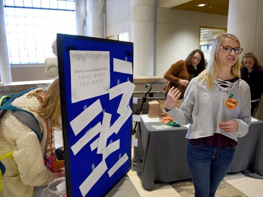 Laurel West, right, from the SGA health and wellness committee talks about Mental health week on UTK campus which strives to raise awareness around the mental health issues facing college students Wednesday, Nov. 29, 2017. At left is student Mary Ciochetty making a positive note for fellow students on the board.