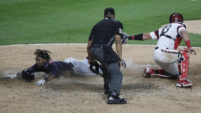 Cleveland Indians' Jose Ramirez, left, scores on a sacrifice bunt by Delino DeShields as Chicago White Sox catcher James MaCann applies a late tag during the 10th inning of a baseball game in Chicago, Sunday, Aug. 9, 2020.