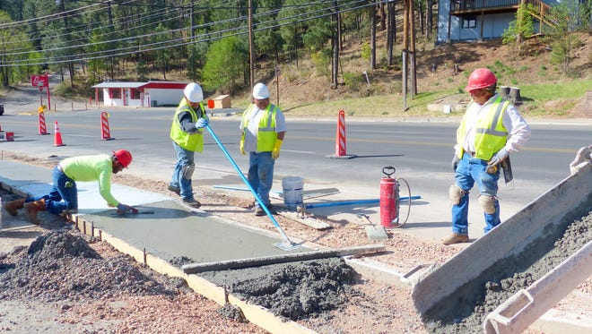Crews from the state Department of Transportation pour and smooth cement to replace sidewalks from River Trail to Country Club Drive on Sudderth Drive in Ruidoso.
