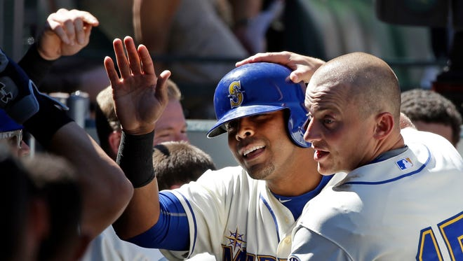 Seattle Mariners' Nelson Cruz, center, is congratulated after his home run by Kyle Seager (15) and teammates against the Texas Rangers in the sixth inning of a baseball game Sunday, Aug. 9, 2015, in Seattle. The Mariners won 4-2.
