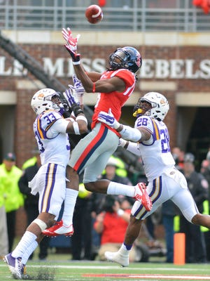 Mississippi Rebels wide receiver Quincy Adeboyejo (8) attempts to make a catch as he is defended by two LSU players.