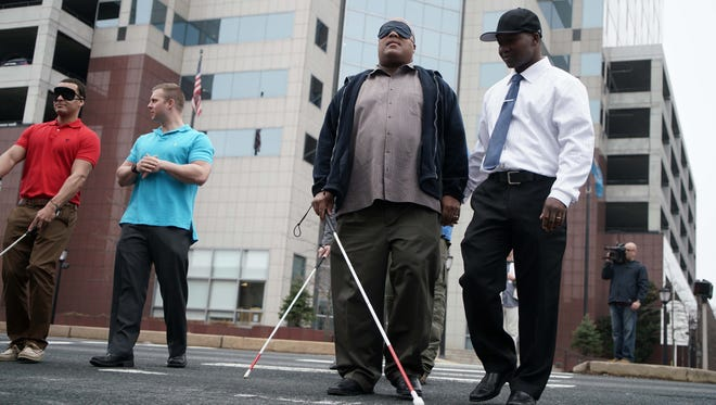 (left to right)Master Corporal Anthony Johnson is guided across Walnut Street with a blindfold by Officer Zonyiho Dongbetor, both with the City of Wilmington Police Department, during a training session with the Delaware Division for the Visually Impaired.