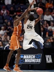 Nevada guard Jordan Caroline shoots against Texas center Mohamed Bamba in the second half of a first round NCAA tournament game.