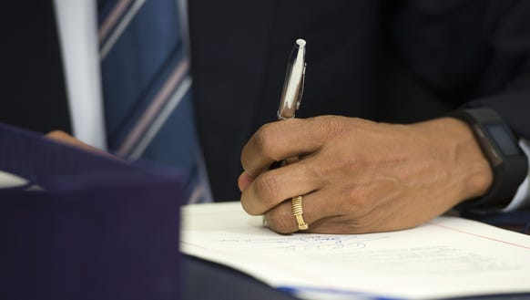 President Obama signs paperwork in the Oval Office