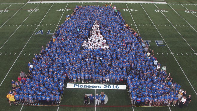 The incoming class of Alfred State students line up for a picture on the football field.