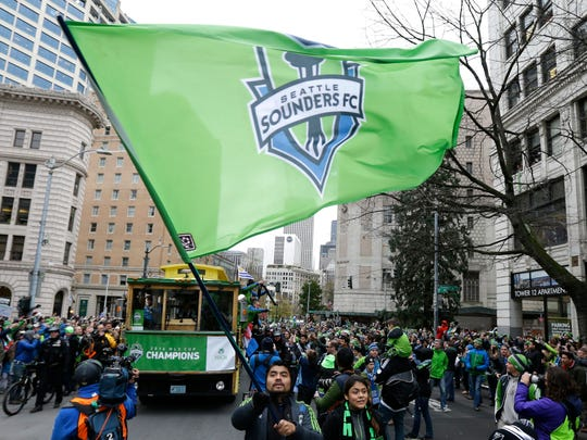 A Seattle Sounders supporter waves a large flag as players parade in trolleys during a celebration march, Tuesday in Seattle.