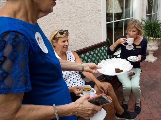 Lenore Farkas offers the final English brownie to Dara Schutte and Mary Beth Conlon of the Naples Newcomers Club North at Bramble's English Tea Room on Wednesday, Oct. 26, 2016, in downtown Naples during the Naples Chocolate Stroll. Participants visited eight shops along Fifth Avenue for chocolate treats.