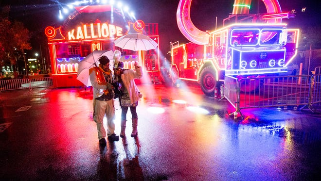 Robert Farthing and Anna Warble look at pictures the shot at the Circle K New Year's Eve Block Party in Tempe December 31, 2014.