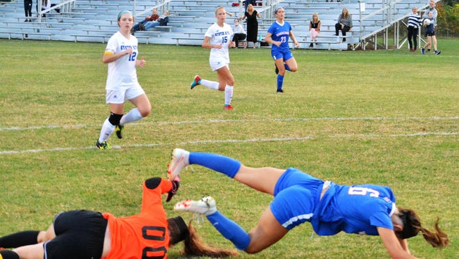 Winnacunnet's Brenna Bushe falls to the ground after colliding with Oyster River goalie Ella Gianino in the second half of Tuesday's girls soccer game in Hampton.