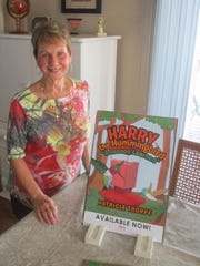 """Patricia Thorpe poses with her first book, """"Harry the Hummingbird: 'A Lesson Learned.'"""""""