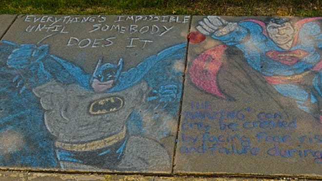 Rebecca Langley, parent of two Meadowlark Elementary School students, put inspirational sayings from Batman and Superman on the sidewalk at the Meadowlark Elementary School, 2200 Glen Ave., in Salina. The sidewalks halfway around the school contained sidewalk drawings from the students who left messages to other students and their teachers a week before school will be starting.