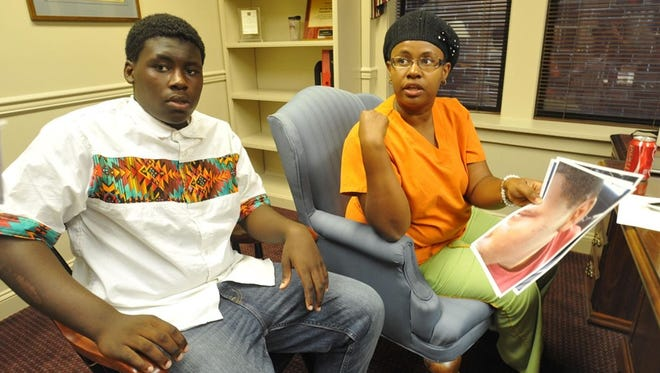 Renaldo Mesadieu, left, and his mother, Nathalie Francois, talk about the lawsuit Attorney Luke Rommel has filed in U.S. District Court against Salisbury Police Officer Justin Aita and Salisbury Police Department in Rommel's Salisbury office Monday. In Francois' hand are photos of the injuries they say Mesadieu suffered.