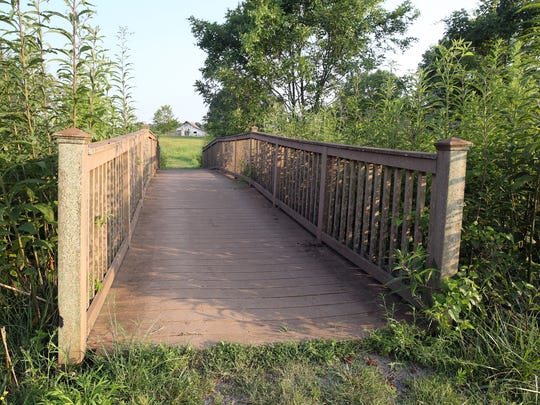 A bridge allows residents of Carothers Farms to cross a stream in their neighborhood park.