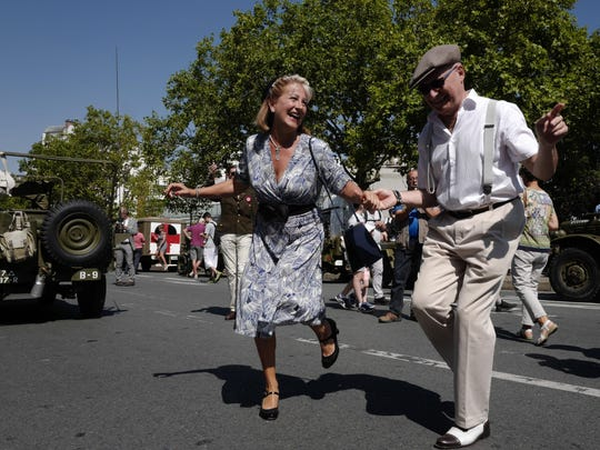 People dressed in World War II era clothes dance during celebrations of the liberation of Paris from Nazi occupation exactly 75 years ago, in Paris, Sunday, Aug. 25, 2019. People dressed in World War II-era military uniforms and dresses are parading in southern Paris, retracing the entry of French and U.S. tanks into the city on Aug. 25, 1944. (AP Photo/Michel Spingler)