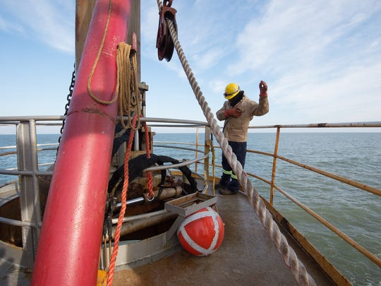 Pablo Solano, a drag tender with Great Lakes Dredge & Dock Company, connects the probe to the bell to begin the process of pumping sand onto Dewey Beach in this file photo. The company has begun a new round of beach nourishment project in Rehoboth Beach and Dewey Beach.